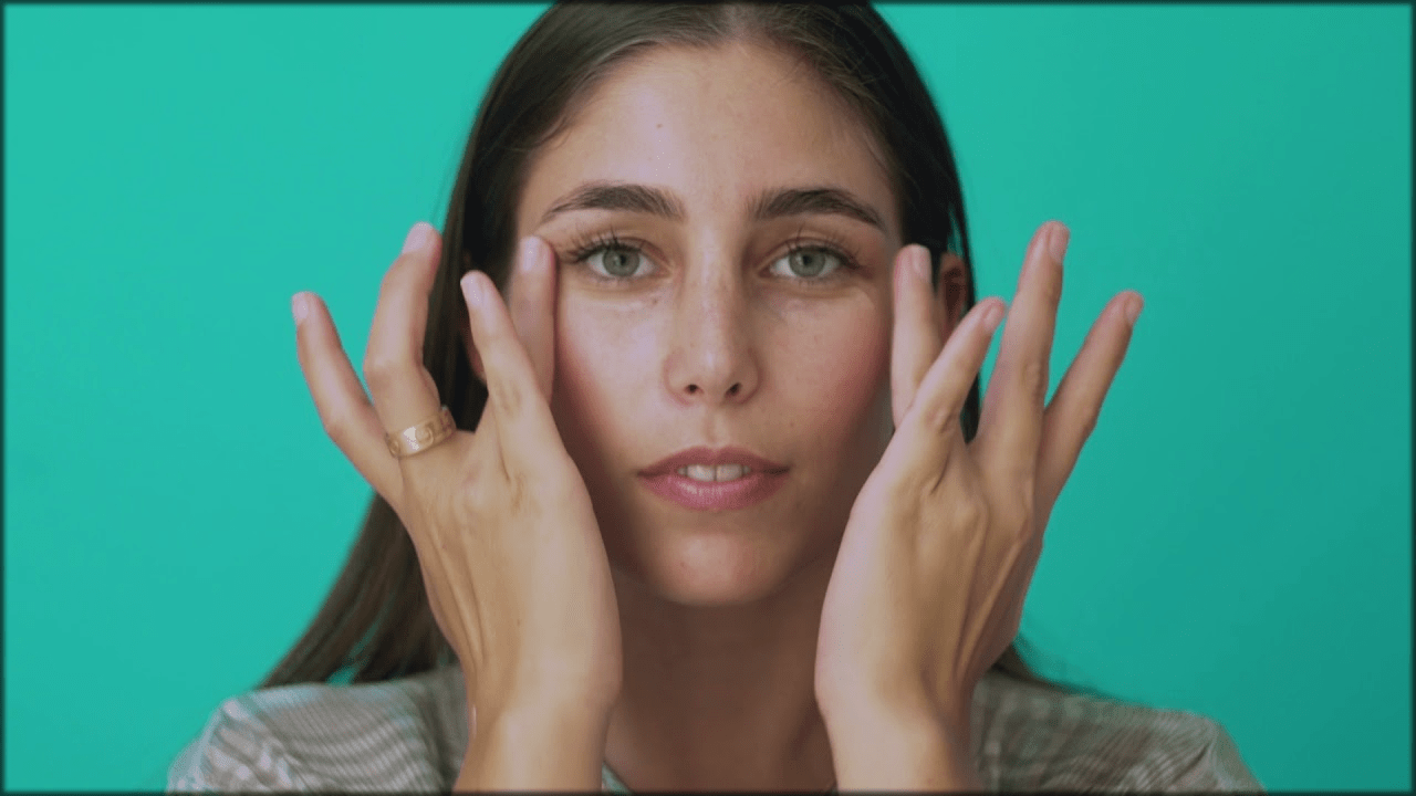 Applying moisturizer to make Eyes look bigger with makeup