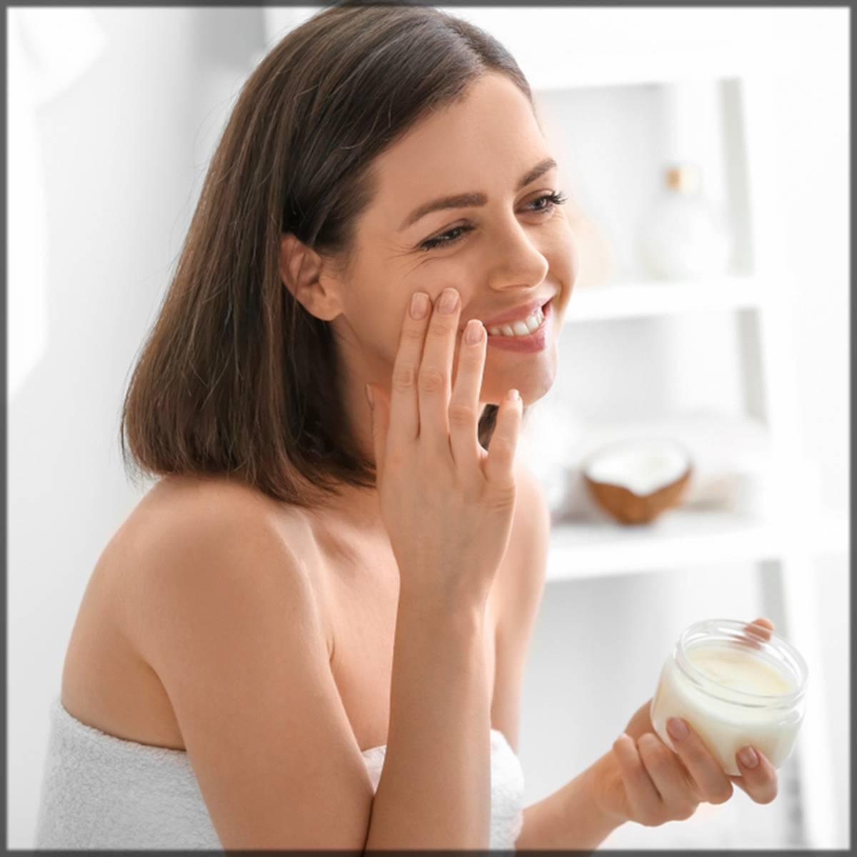 girl applying coconut oil on skin tags